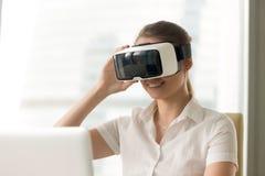 微笑的妇女尝试的vr风镜,前第一件虚拟现实的盔甲 免版税库存照片