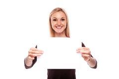 微笑的妇女展示大空白的委员会 免版税库存照片