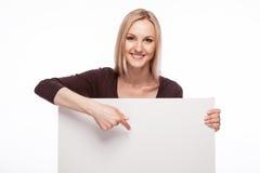 微笑的妇女展示大空白的委员会 免版税库存图片