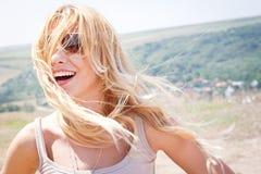 微笑的妇女户外与风吹的头发 免版税库存图片