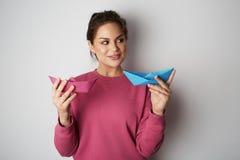 微笑的妇女拿着两蓝色的和桃红色颜色纸在空的灰色背景运送 情感,人们,秀丽,时尚 免版税库存图片