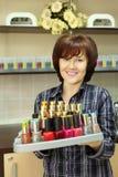微笑的妇女拿着指甲油 库存照片