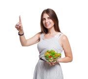 微笑的妇女拿着新鲜蔬菜沙拉并且接触虚构的屏幕 库存照片