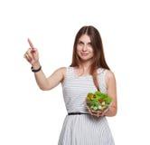 微笑的妇女拿着新鲜蔬菜沙拉并且接触虚构的scr 免版税库存照片