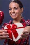 微笑的妇女拿着有红色丝带的白色礼物盒 免版税库存图片