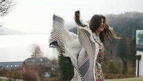 微笑的妇女拿着格子花呢披肩和愉快地跑并且转动在周围在春天山的背景 影视素材