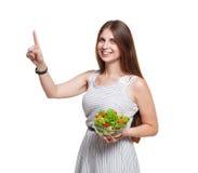 微笑的妇女拿着菜沙拉并且接触虚构的屏幕 库存照片