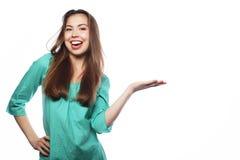 年轻微笑的妇女指向有正面面部expressio的一只手 免版税库存照片