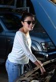 微笑的妇女检查汽车油 库存照片