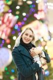微笑的妇女照片外套的有在圣诞树背景的礼物盒的在商店 免版税库存图片