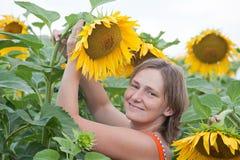 微笑的妇女用向日葵 免版税图库摄影