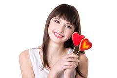 微笑的妇女用心形的饼干 免版税库存照片