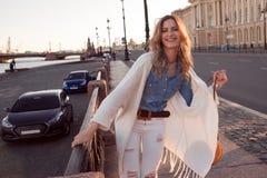 微笑的妇女画象一件白色羊毛衫的 街道背景的笑的女孩  免版税库存照片