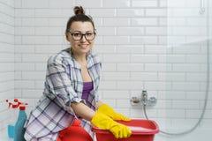 微笑的妇女画象玻璃的,做房子清洁,女性清洗的卫生间的橡胶手套 免版税库存照片