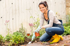 微笑的妇女秋天从事园艺的后院爱好 免版税库存图片