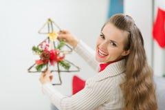 微笑的妇女藏品圣诞节装饰结构树 库存图片