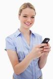 微笑的妇女藏品她的移动电话 免版税库存图片
