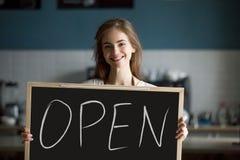 微笑的妇女藏品打开标志黑板邀请到新的咖啡馆 免版税库存图片