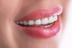微笑的妇女装腔作势地说与在白色背景的伟大的牙 库存照片