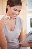 微笑的妇女读取报纸,当食用茶时 图库摄影