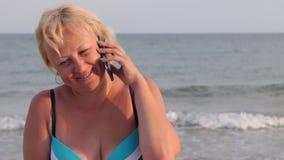 微笑的妇女谈话由在海滩的电话 影视素材