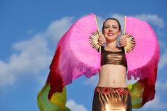 微笑的妇女跳舞与桃红色面纱风扇 免版税库存图片