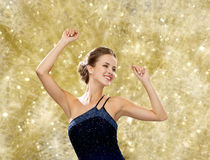 微笑的妇女跳舞用被举的手 免版税库存图片