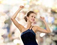 微笑的妇女跳舞用被举的手 免版税图库摄影