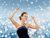 微笑的妇女跳舞用被举的手 库存照片
