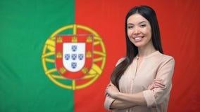 微笑的妇女身分用手横渡反对葡萄牙旗子背景 影视素材