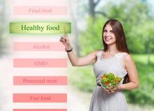 微笑的妇女选择在未来派屏幕上的健康食物 免版税图库摄影