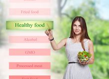 微笑的妇女选择在未来派屏幕上的健康食物 库存照片