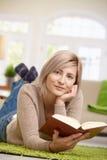 微笑的妇女阅读书 图库摄影
