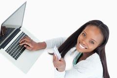 微笑的妇女预订飞行在线 库存图片