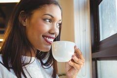 微笑的妇女食用咖啡在办公室 免版税库存图片