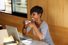 微笑的妇女饮用的咖啡和看膝上型计算机 免版税库存图片