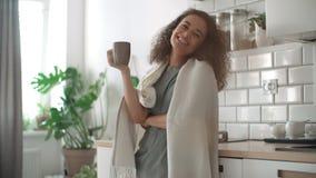 微笑的妇女饮用的咖啡或茶画象在家 免版税库存照片