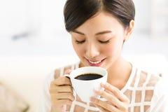 年轻微笑的妇女饮用的咖啡早晨 免版税库存照片