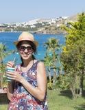年轻微笑的妇女饮用的咖啡画象在海背景的 图库摄影