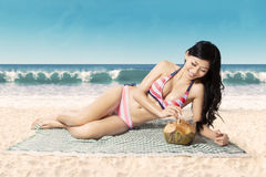 微笑的妇女饮用的椰子水 免版税库存照片