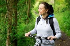微笑的妇女骑马自行车 图库摄影