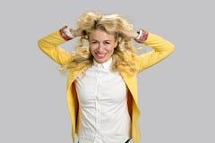 年轻微笑的妇女,在头发的手 库存照片