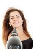 微笑的妇女,当吹干送在她的头发时的空气 免版税库存照片