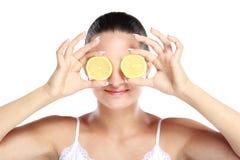 微笑的妇女,当拿着切片在她的眼睛前面时的柠檬 免版税库存照片