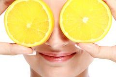 微笑的妇女,当拿着切片在她的眼睛前面时的柠檬 图库摄影