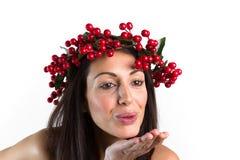 微笑的妇女,有在她的头的圣诞节花圈的,送一个亲吻 图库摄影