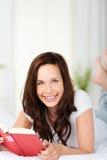 微笑的妇女读书在床上 库存图片