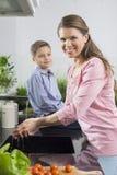 微笑的妇女洗涤的手画象有儿子的坐柜台在厨房里 库存照片