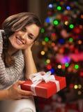 微笑的妇女画象在拿着当前箱子的圣诞树附近的 免版税库存照片