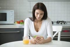 微笑的妇女画象有吃的智能手机的健康午餐 免版税库存照片